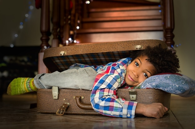 Chłopiec budzi się w walizce. energiczny poranny uśmiech afro dzieciaka. nowy dzień nowa podróż. czas na przygody.