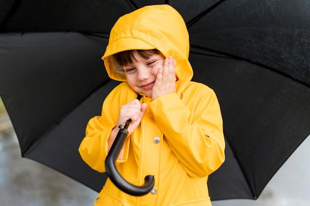 Chłopiec buźkę trzymając otwarty parasol
