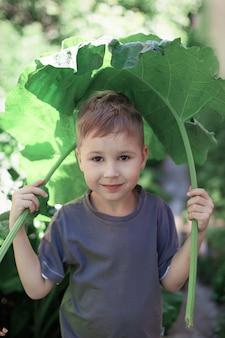 Chłopiec był pokryty liśćmi łopianu przed deszczem
