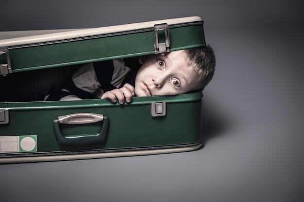 Chłopiec chowa się w starej walizce
