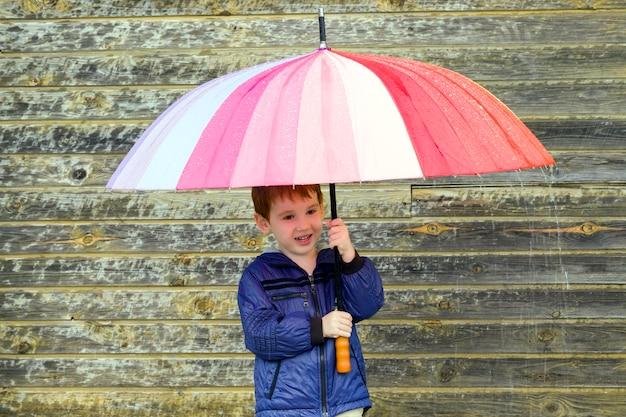 Chłopiec chowający się pod różnokolorowym parasolem w deszczową pogodę, zbliżenie radującego się dziecka, które ukryło się przed deszczem