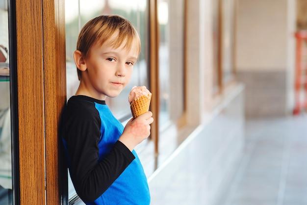 Chłopiec cieszy się smakowitych owocowych lody. letnie wakacje. słodkie jedzenie i desery. lody w rożku waflowym.