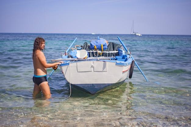 Chłopiec cumuje łódź na plaży porticello