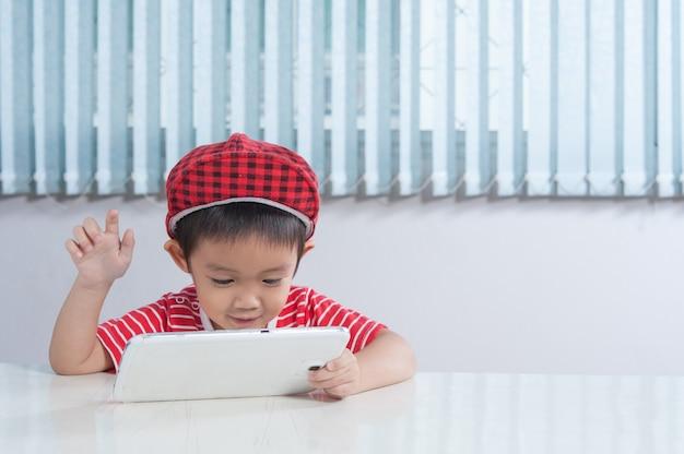 Chłopiec cute odtwarzanie tabletek w pokoju dla dzieci