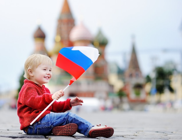 Chłopiec cute za toddler siedzi i gra z flagą rosyjski z placu czerwonego i zejście vasilevsky