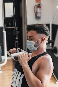 Chłopiec ćwiczący na bloczku gimnastycznym z maską