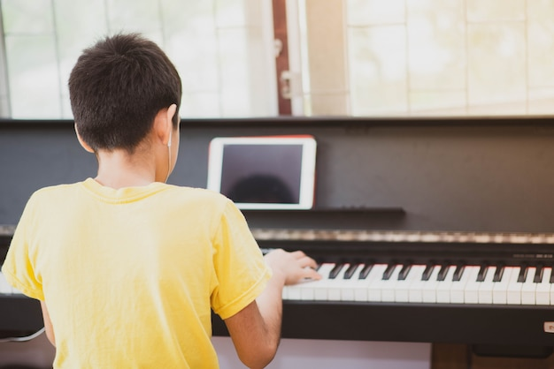 Chłopiec ćwiczy fortepianową online cyfrową pastylkę w domu