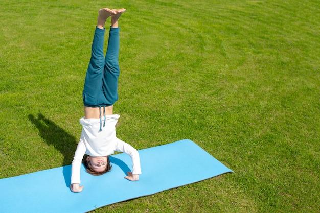 Chłopiec ćwiczy jogę na trawie. zajęcia na świeżym powietrzu dla dzieci