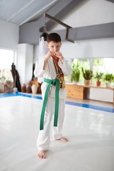 Chłopiec ćwiczy kimono z medalikami na szyi