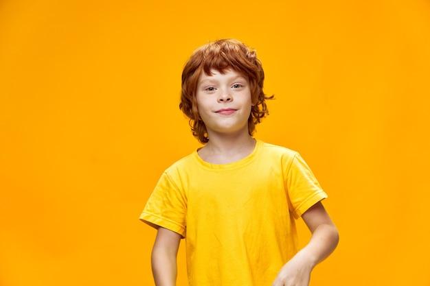 Chłopiec czerwone włosy żółta koszulka na białym tle przycięty widok