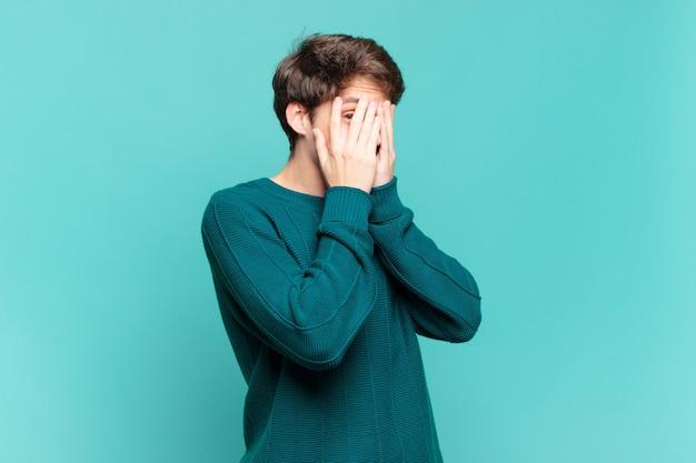 Chłopiec czuje się przestraszony lub zawstydzony, zerka lub podgląda z oczami na wpół zakrytymi rękoma