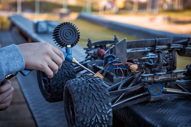 Chłopiec czyści swój samochód rc za pomocą sprężarki powietrza