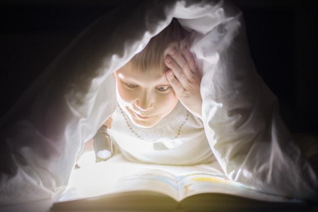 Chłopiec czyta książkę pod kocem z latarką