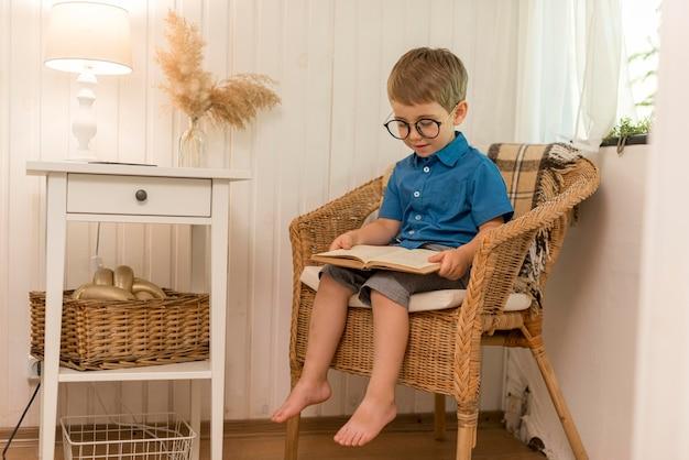 Chłopiec czyta siedząc w fotelu