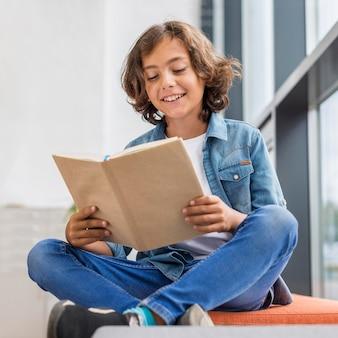 Chłopiec czytający z książki obok okna