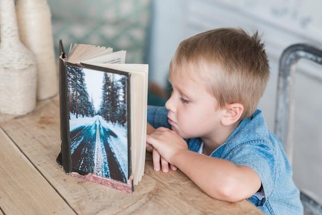 Chłopiec czytelnicza książka przy łomotać stół