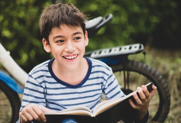 Chłopiec czytelniczej książki obsiadanie z bicyklem w parku