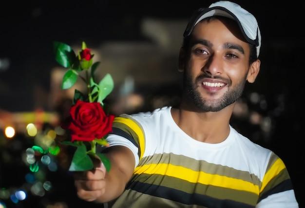 Chłopiec dający różę swojemu kochankowi - czerwona róża w ręku
