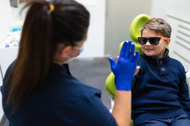 Chłopiec daje dentystowi pięć
