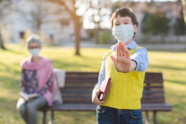 Chłopiec daje przerwa znakowi pyta dla ogólnospołecznego dystansowania, ostrość na ręce