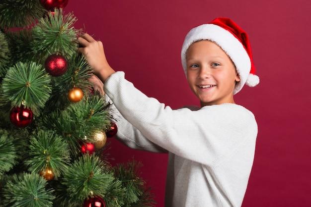 Chłopiec dekoruje choinka środka strzał