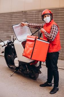 Chłopiec dostarczający jedzenie jeżdżący skuterem z pudełkiem z jedzeniem i noszącym maskę