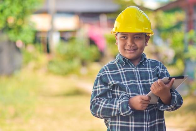 Chłopiec dzieciaka chwyta pastylki use ciężkiego kapeluszu inżyniera budowa