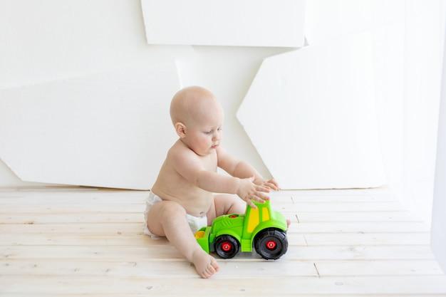 Chłopiec dziecko 8 miesięcy siedzi w pieluchach z zieloną maszyną do pisania zabawki w oknie, miejsce na tekst