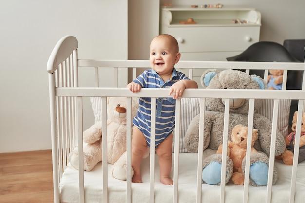 Chłopiec dziecko bawi się drewnianymi zabawkami w pokoju dziecięcym w jasnych kolorach, w dziecięcej sypialni w stylu skandynawskim