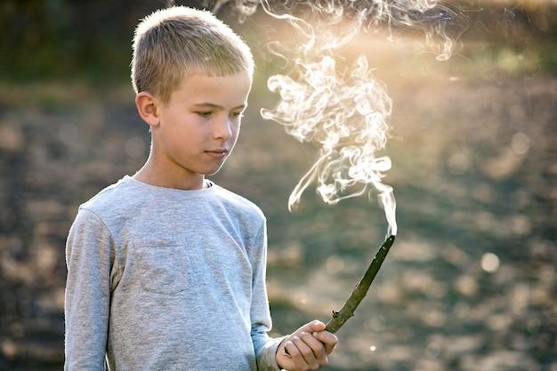Chłopiec dziecko bawi się paląc drewniany kij na zewnątrz.