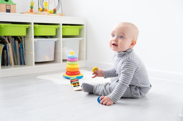 Chłopiec dziecko bawi się w piramidzie i drewniane zabawki. wczesny rozwój dzieci.