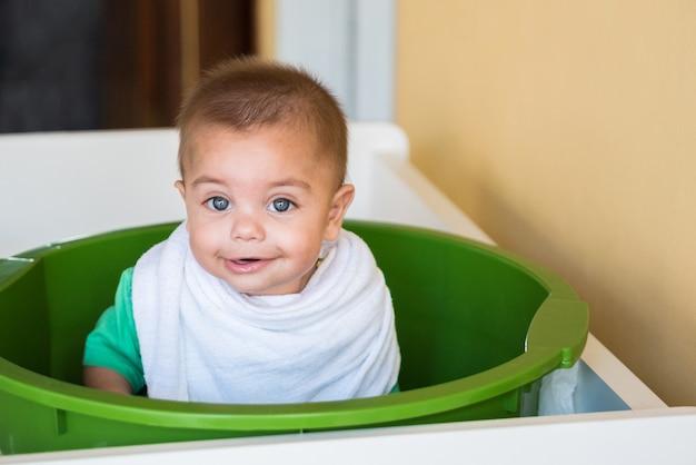 Chłopiec dziecko bawiące się w plastikowej umywalce - z pieluchą na szyi