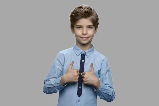 Chłopiec dziecko dając kciuki do góry na szarym tle. portret przystojny dzieciak daje znak zatwierdzenia na szarym tle.