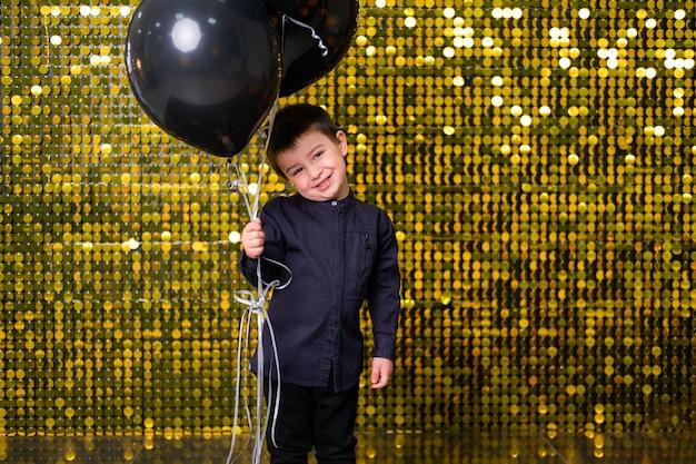 Chłopiec dziecko gospodarstwa czarne balony na tle ze złotymi błyszczącymi cekinami, paillettes.