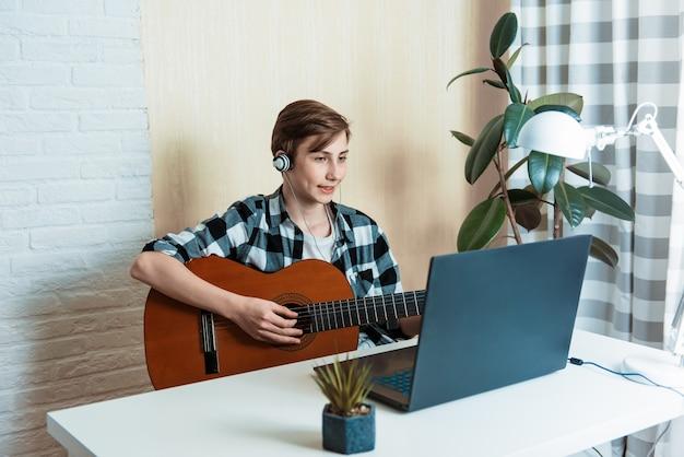 Chłopiec dziecko gra na gitarze i ogląda lekcje online na laptopie podczas ćwiczeń w domu. szkolenia online, zajęcia online