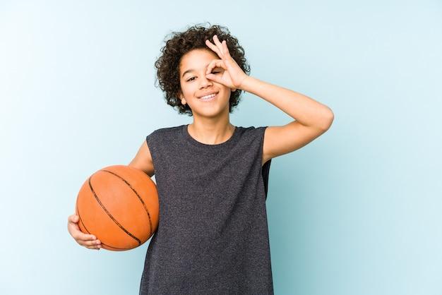Chłopiec dziecko gra w koszykówkę na białym tle na niebieskiej ścianie podekscytowany, utrzymując ok gest na oko.