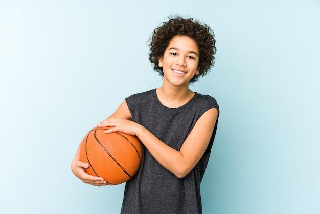 Chłopiec dziecko gra w koszykówkę na białym tle na niebieskiej ścianie, śmiejąc się i zabawy.