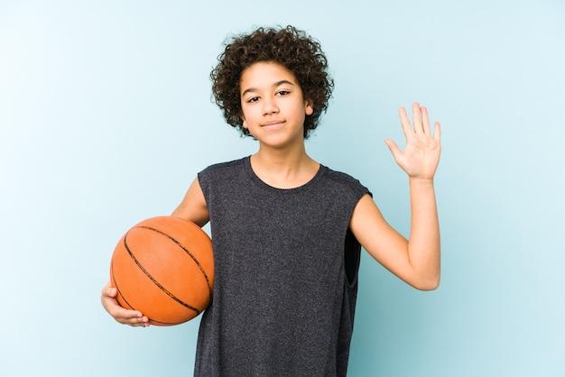 Chłopiec dziecko gra w koszykówkę na białym tle na niebieskiej ścianie uśmiechnięty wesoły pokazując numer pięć palcami.
