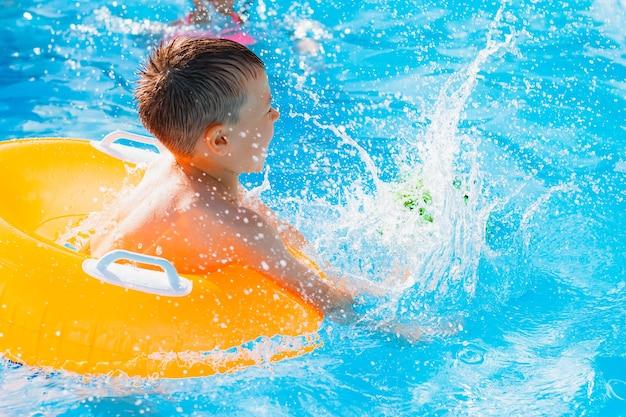 Chłopiec dziecko grając w odkrytym basenie ośrodka. w nadmuchiwanym żółtym kółku z piłką. dzieci bawią się zabawkami wodnymi. rozpryskiwanie się. wyluzuj ciepło.