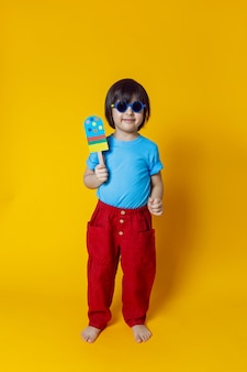 Chłopiec dziecko je lody z kolorowego papieru na żółtej ścianie