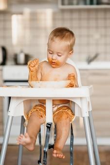 Chłopiec dziecko jedzenie makaronu rękami