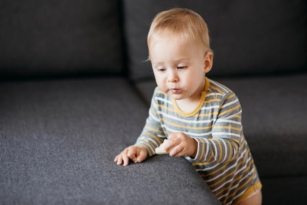 Chłopiec dziecko jedzenie obok sofy