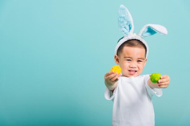 Chłopiec dziecko ma na sobie uszy królika i biały t-shirt, stojąc do posiadania pisanek