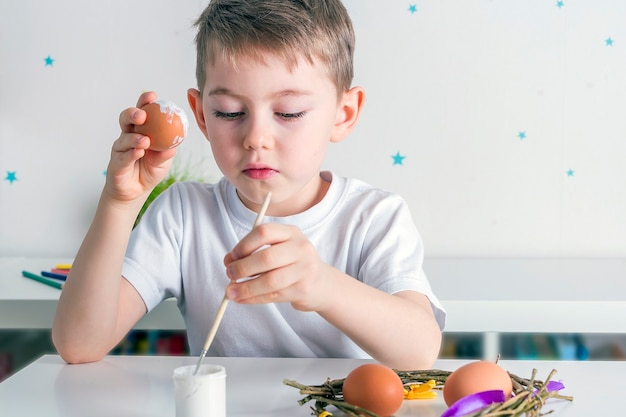 Chłopiec Dziecko Maluje Jajka Białą Farbą. Koncepcja Diy. Premium Zdjęcia