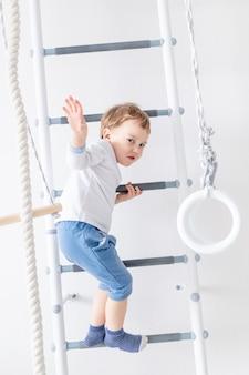Chłopiec dziecko na szwedzkiej ścianie lub kompleksie sportowym wspina się w domu, koncepcja sportu dziecięcego