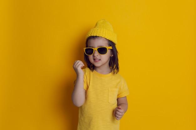 Chłopiec dziecko na żółtej ścianie w kapeluszu i okrągłych okularach przeciwsłonecznych