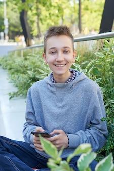 Chłopiec dziecko nastolatek z telefonem komórkowym siedzi i uśmiecha się. nauka online, edukacja na odległość, edukacja domowa.