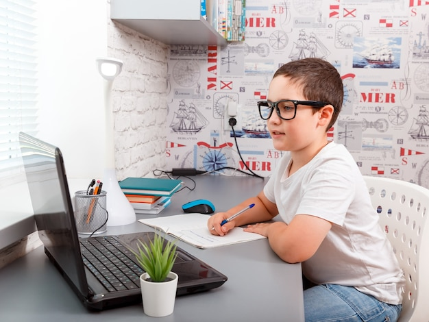 Chłopiec dziecko odrabiania lekcji na laptopie na platformie internetowej
