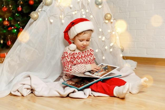 Chłopiec dziecko ogląda album ze zdjęciami w pobliżu choinki nowy rok