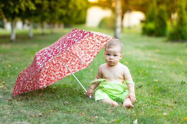 Chłopiec dziecko pod parasolem siedzi na trawniku zielony latem